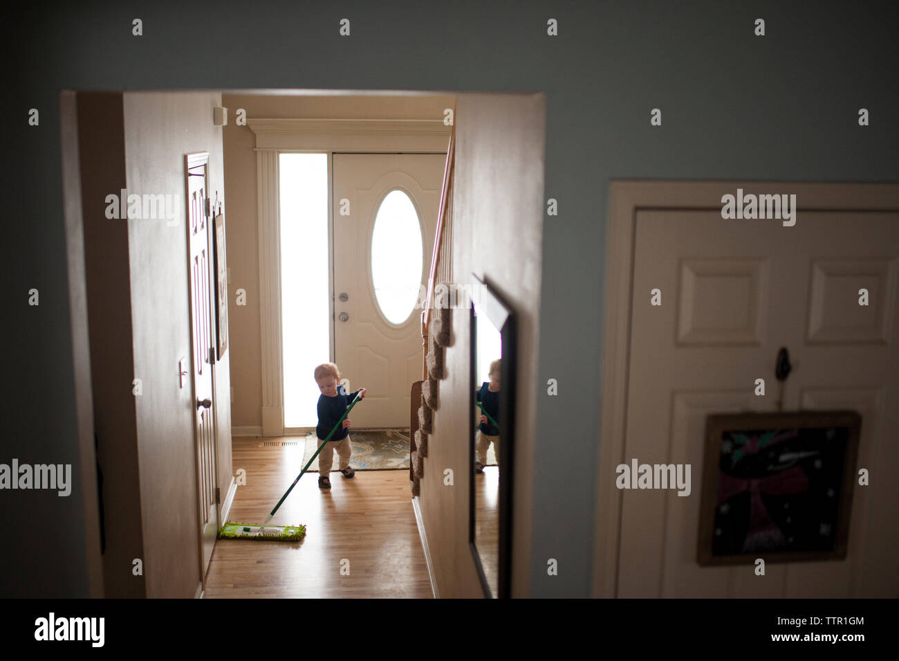 Full length of baby boy wiping hardwood floor with mop at home - Stock Image