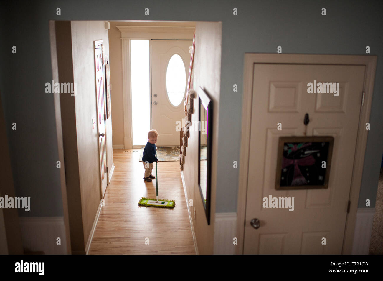Baby boy wiping hardwood floor with mop at home - Stock Image