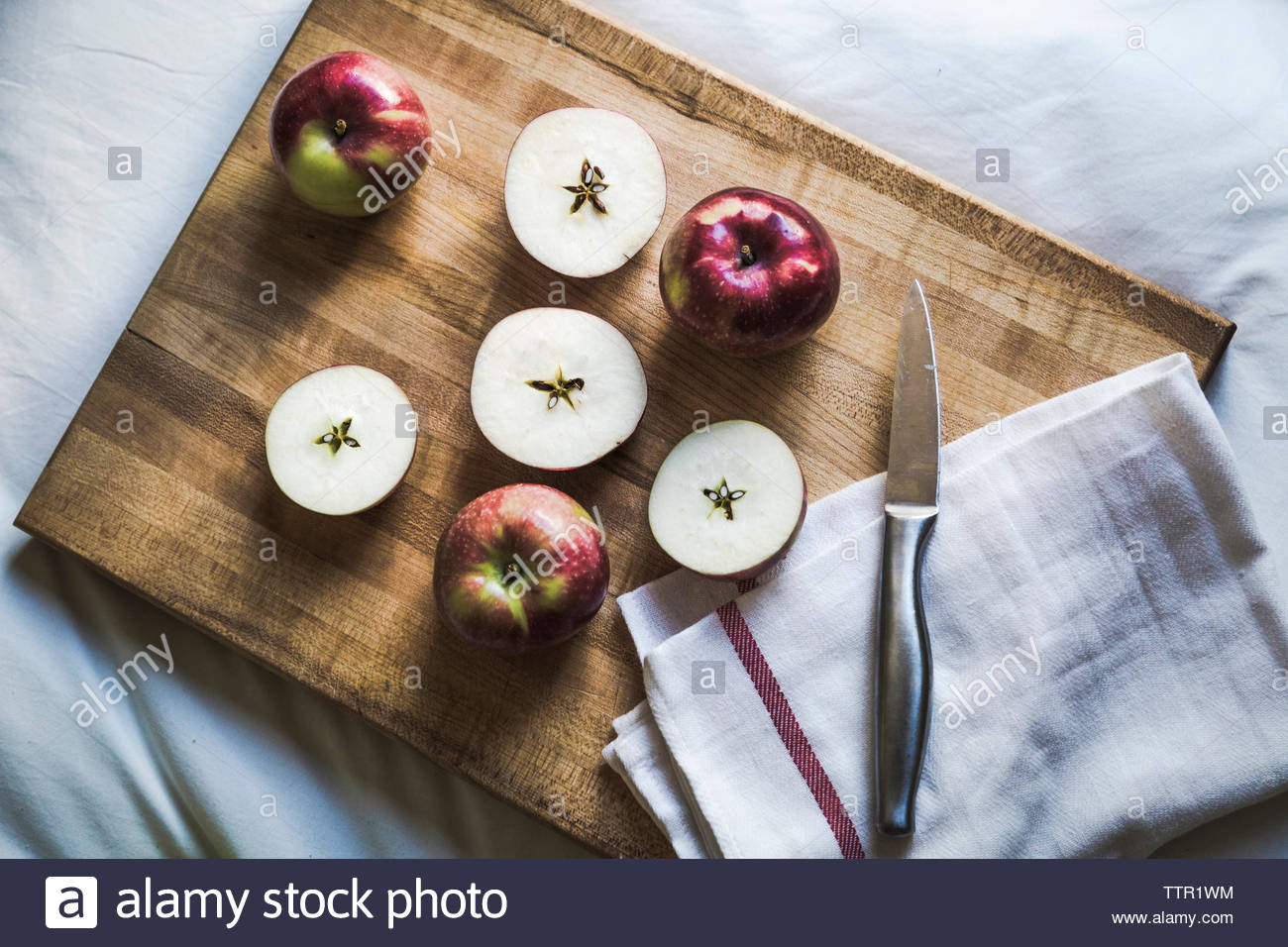 High angle view of apple with kitchen knife and napkin on cutting board - Stock Image