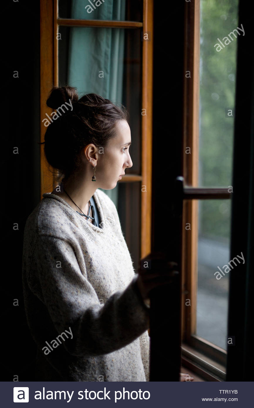 Thoughtful young woman looking through window while standing home - Stock Image