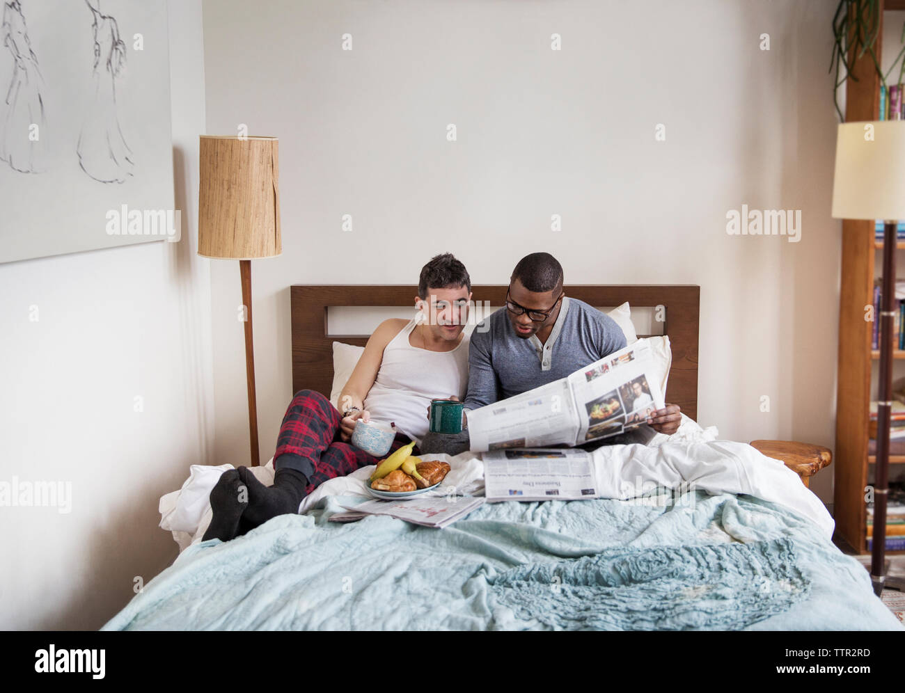 Multi-ethnic homosexual males reading newspaper in bedroom Stock Photo