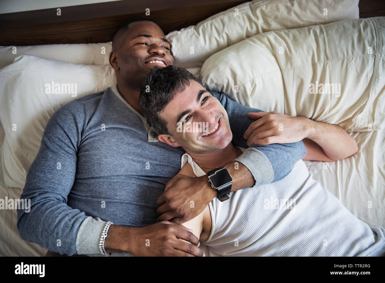 Overhead view of happy loving gay couple lying on bed Stock Photo