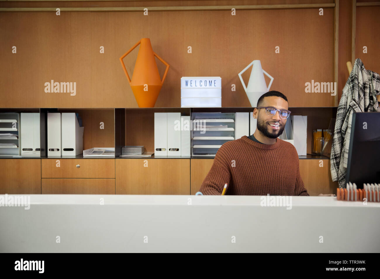 Portrait of businessman sitting by cabinet in office Stock Photo