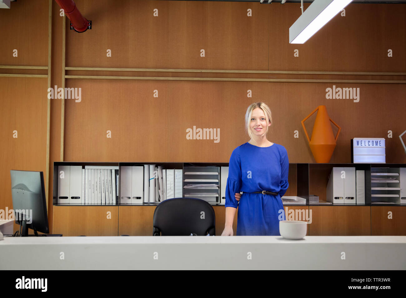 Portrait of smiling businesswoman standing at desk in office Stock Photo