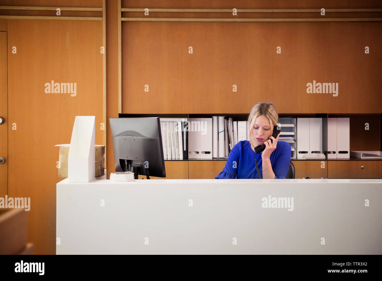 Businesswoman talking on telephone at desk in office Stock Photo