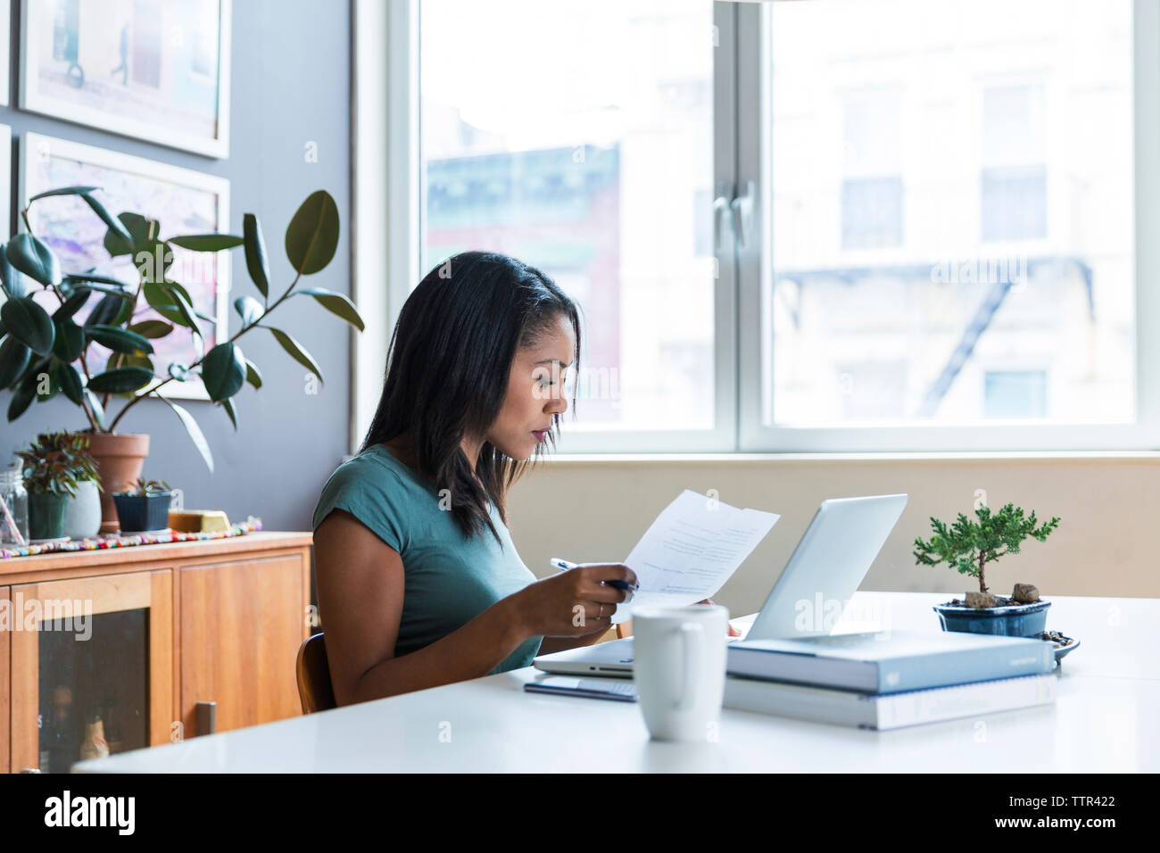 Serious woman working at home office - Stock Image