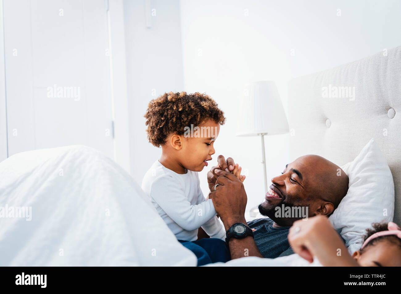Happy father playing with son while relaxing on bed against wall at home Stock Photo
