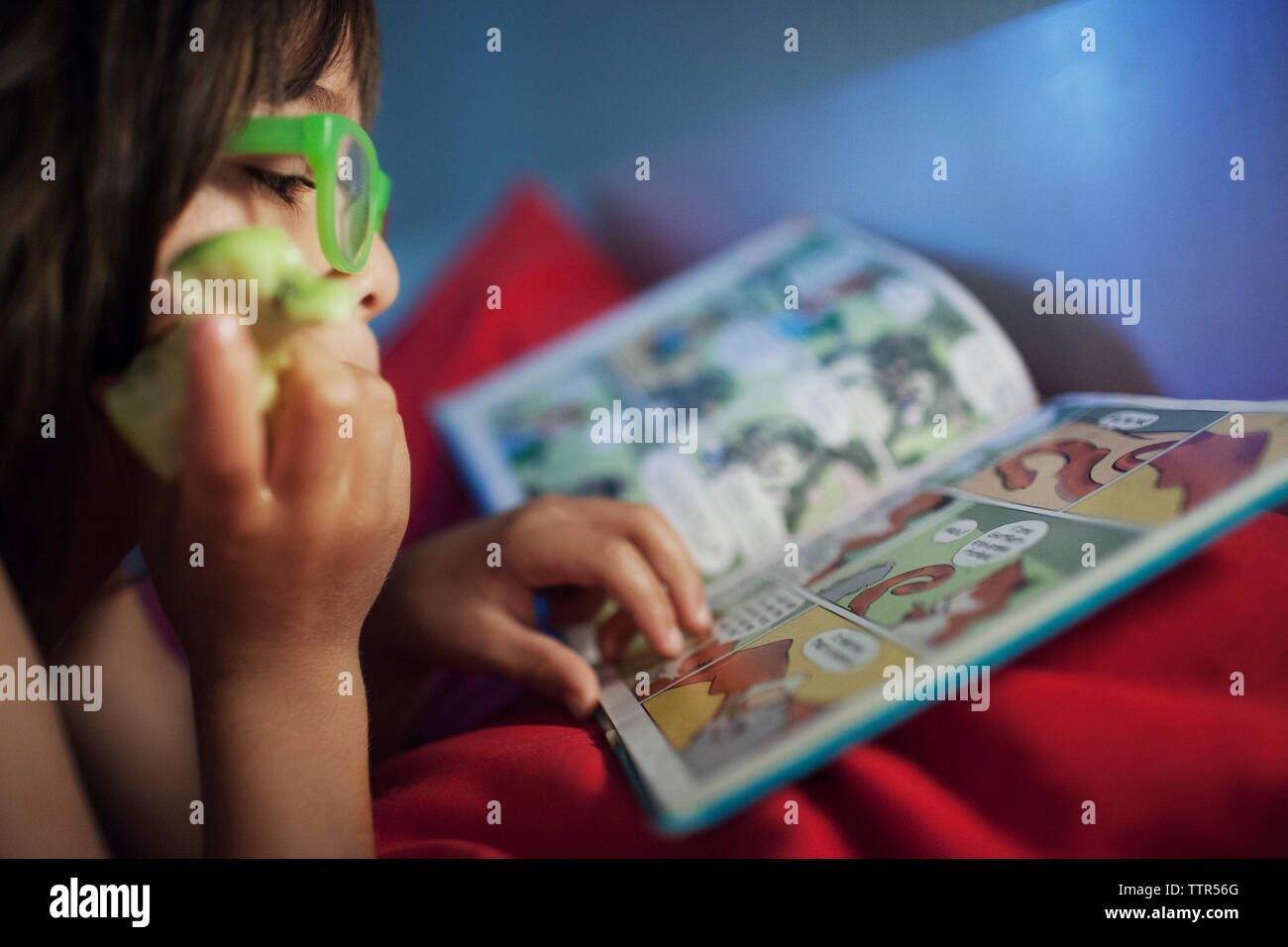 Side view of boy reading story book in bedroom - Stock Image