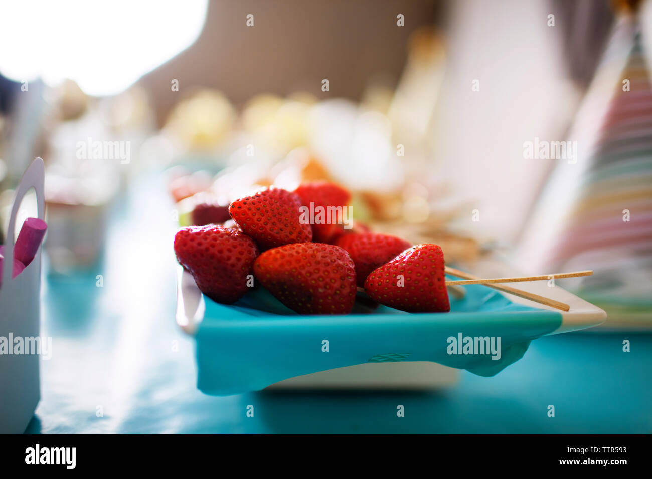 Close-up of strawberries and toothpicks in plate on table - Stock Image
