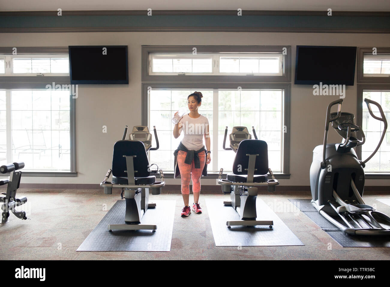 Woman drinking water while standing amidst machines at gym - Stock Image