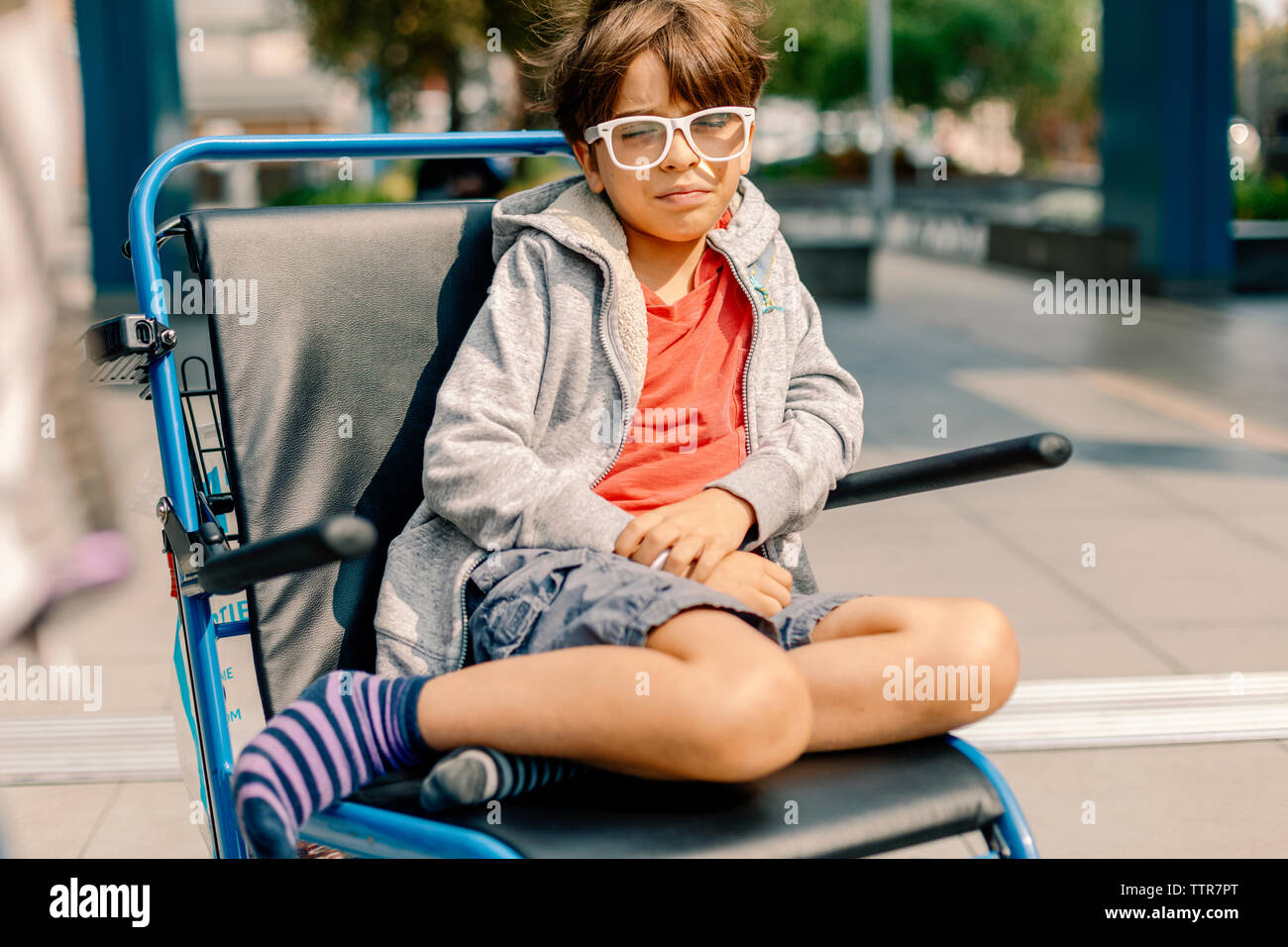 Uncomfortable boy in wheel chair leaving the hospital Stock Photo