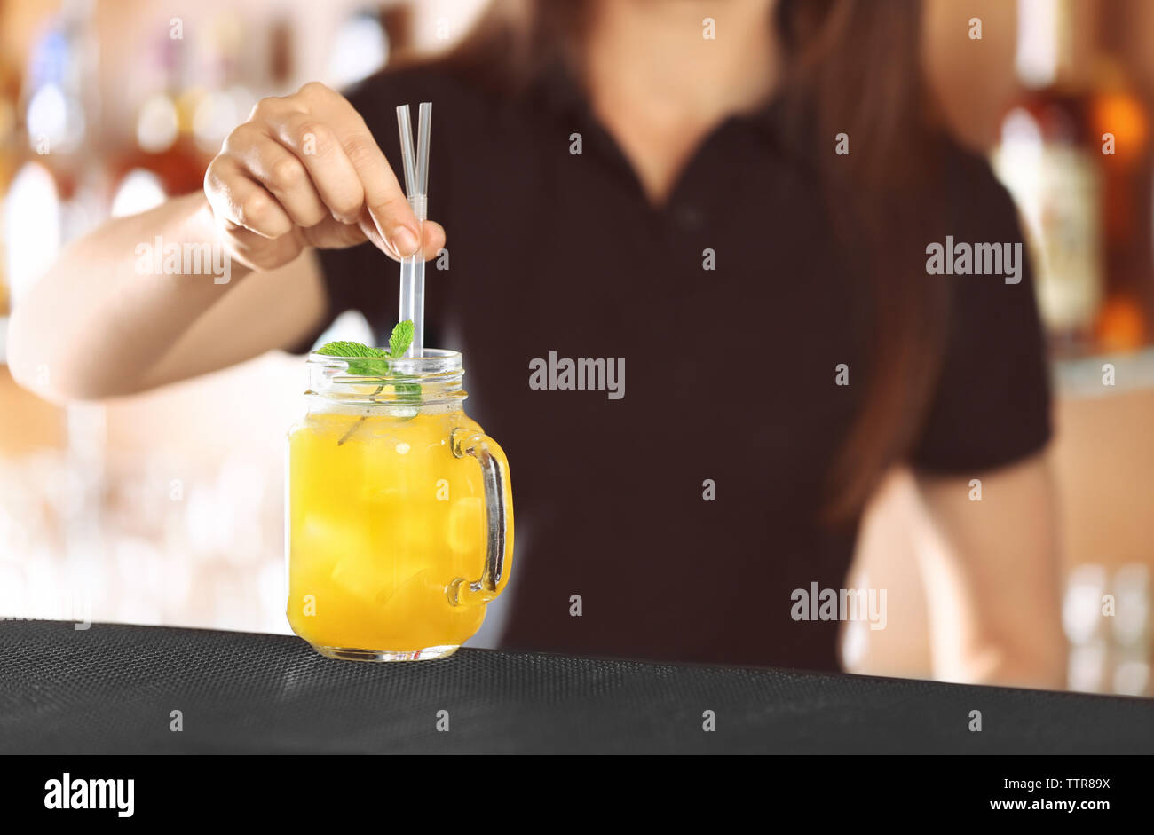 Woman hands putting straws into cocktail on bar counter Stock Photo