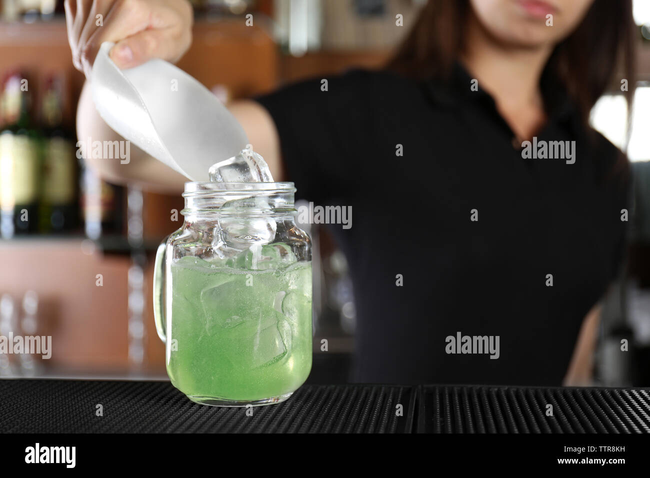 Woman hands adding ice into cocktail on bar counter Stock Photo