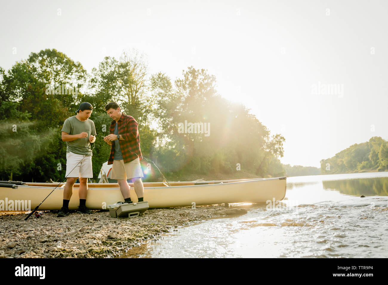 Male friends adjusting fishing tackles while standing by boat at lakeshore - Stock Image