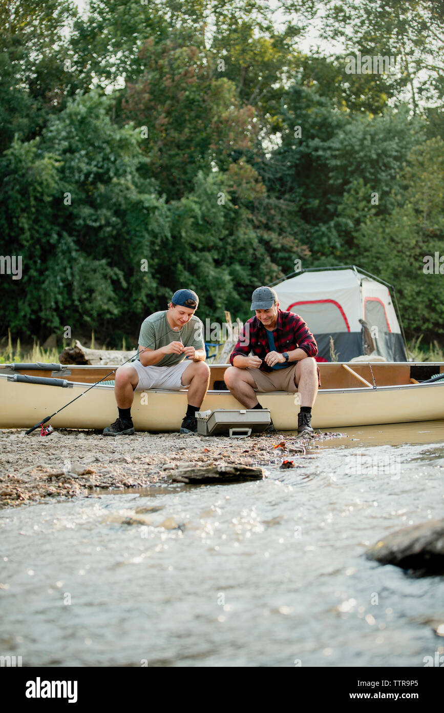 Friends adjusting fishing tackles while sitting on boat by lake at campsite - Stock Image
