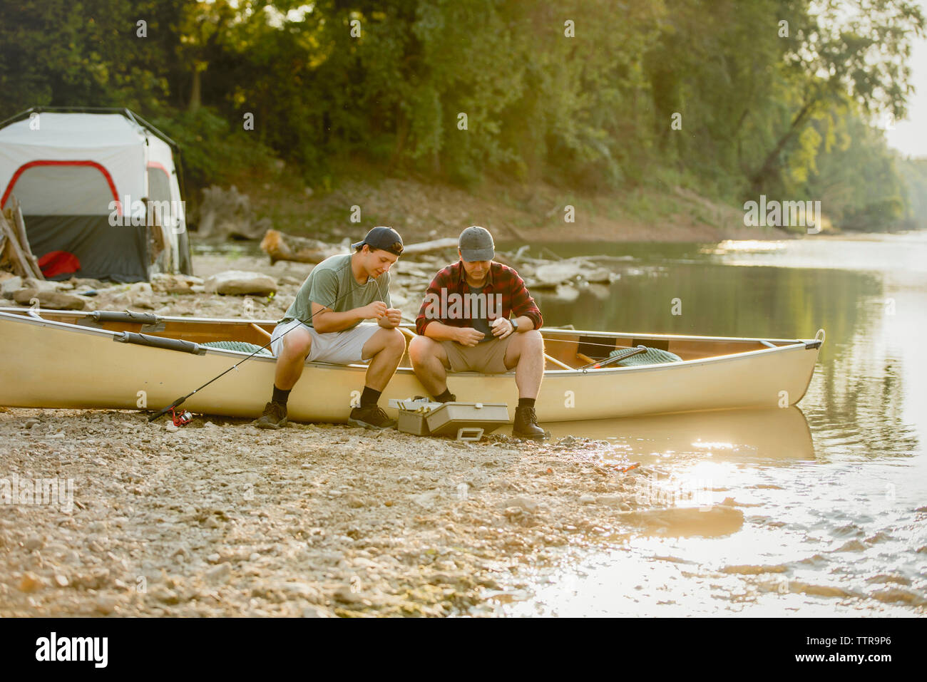 Friends adjusting fishing tackles while sitting on boat at campsite - Stock Image