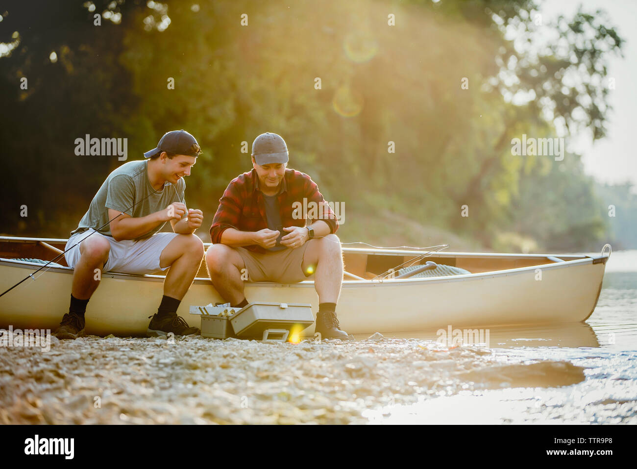 Friends adjusting fishing tackles while sitting on boat by lake - Stock Image