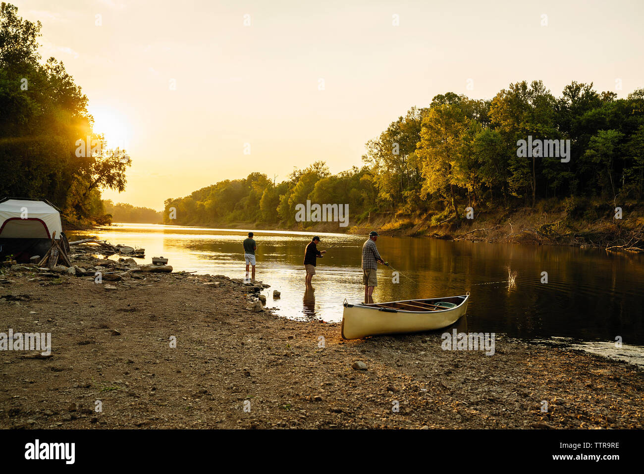 Male friends fishing while standing in lake against clear sky during sunset Stock Photo