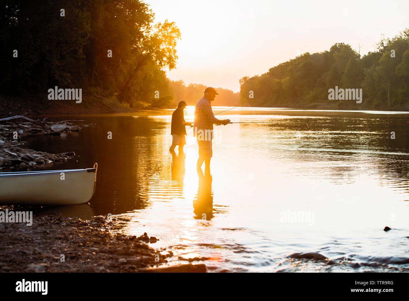 Side view of male friends fishing while standing in lake against clear sky during sunset Stock Photo