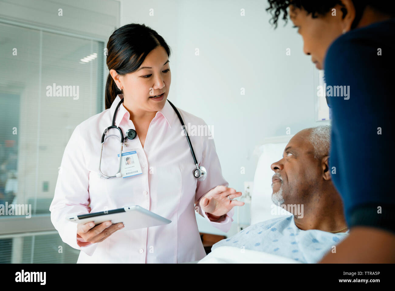 Doctor with tablet computer talking to senior patient lying by daughter in hospital ward Stock Photo