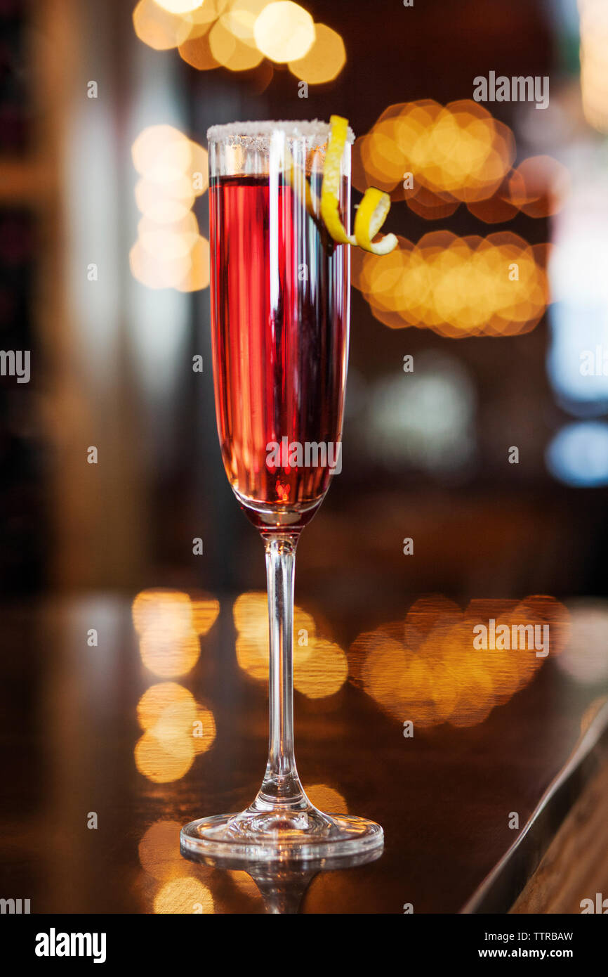 Cocktail served in champagne flute on table at bar - Stock Image