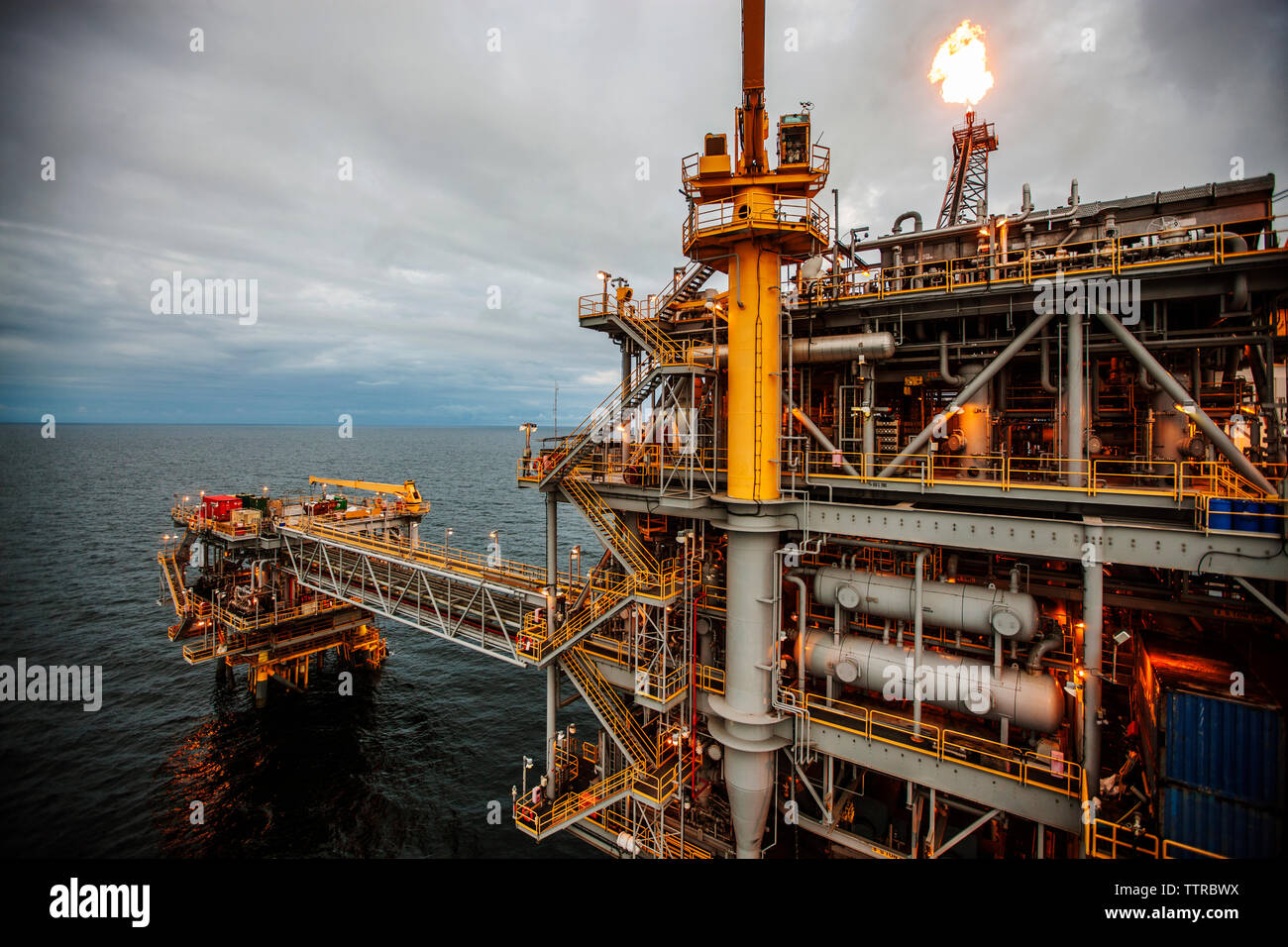 Oil rig in sea emitting fire Stock Photo