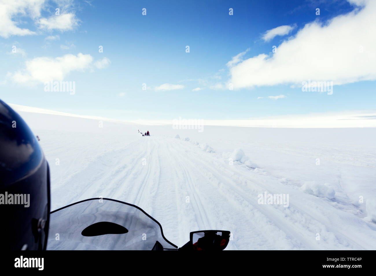 Cropped image of person riding snowmobile on landscape against sky - Stock Image