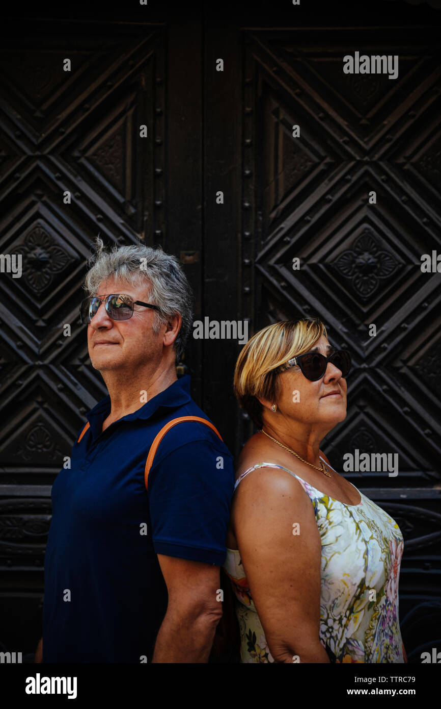 Senior couple wearing sunglasses while standing against closed doors Stock Photo