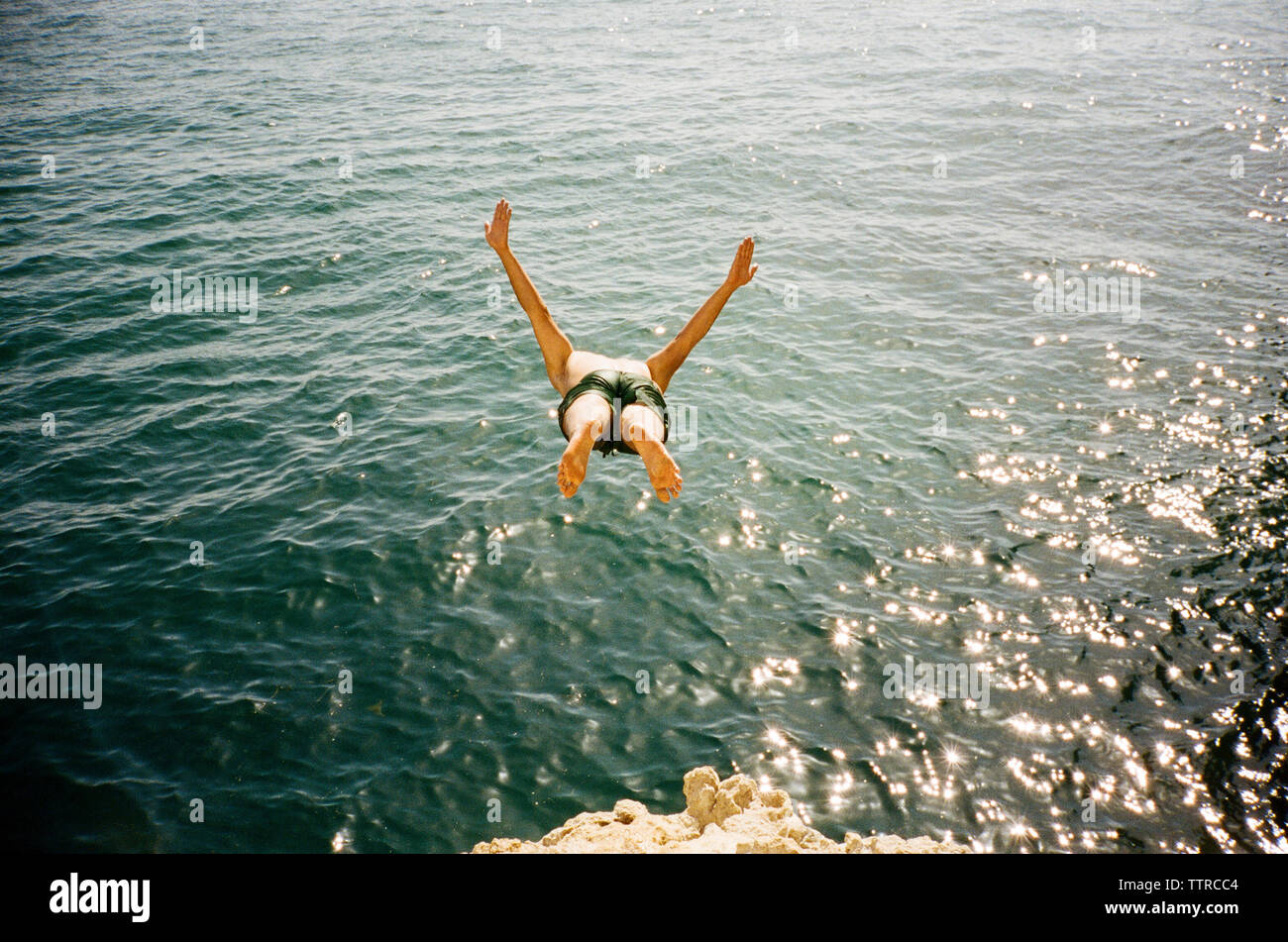 High angle view of man diving into sea - Stock Image