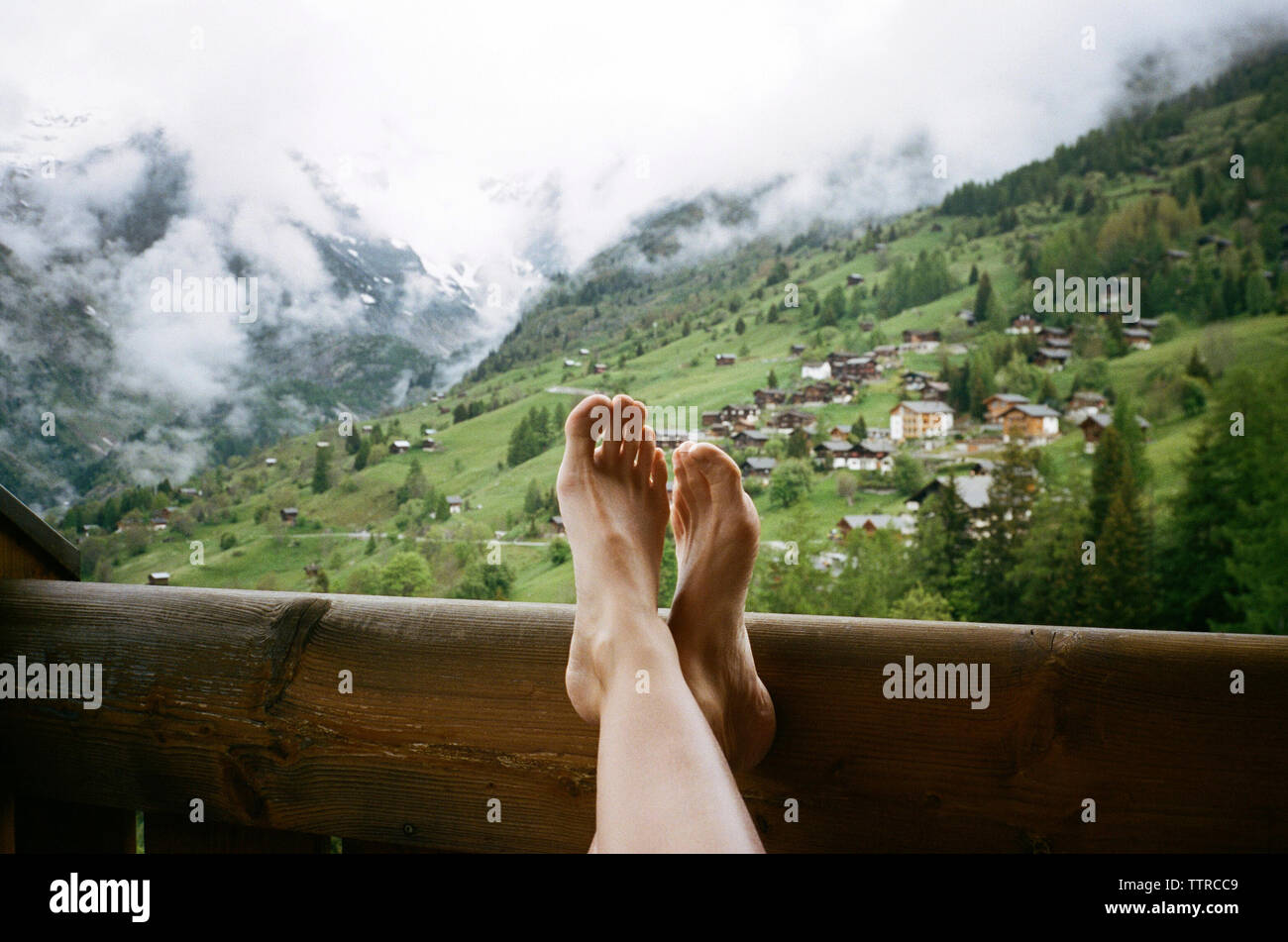 Low section of woman relaxing in balcony against mountains - Stock Image