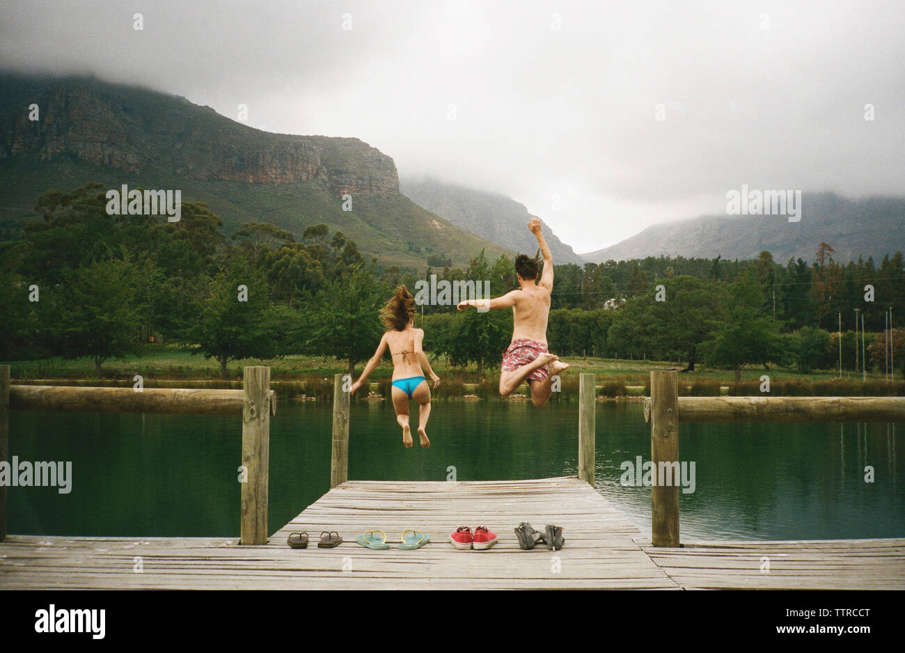 Rear view of excited friends jumping from jetty in lake against mountains - Stock Image