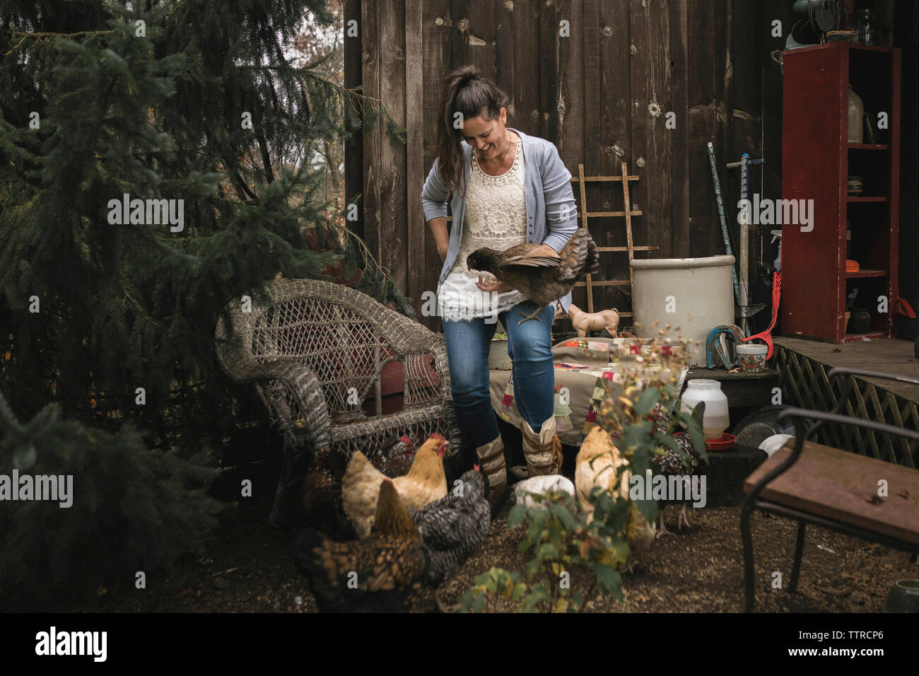 Smiling woman standing by hens in backyard - Stock Image