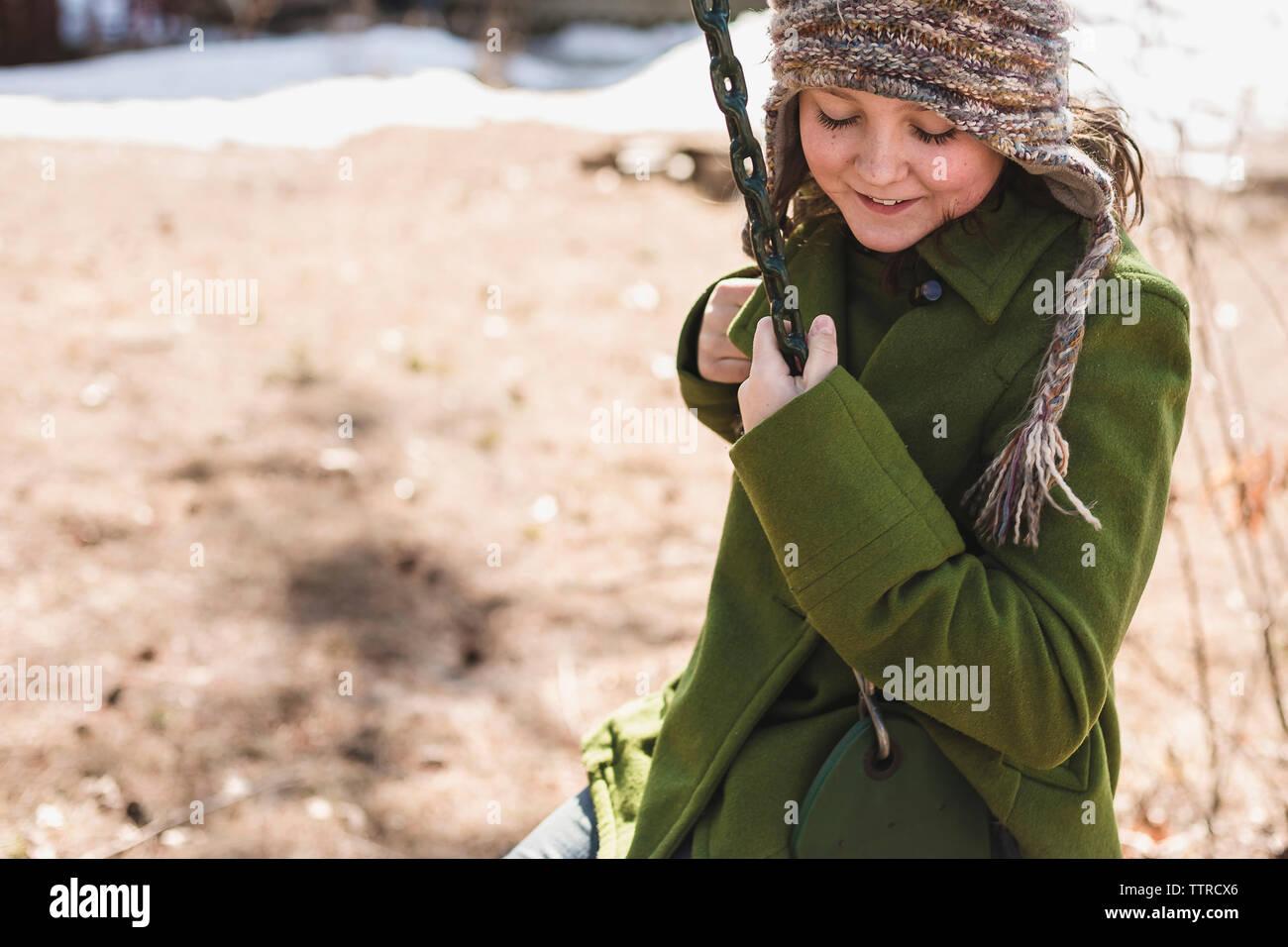 Smiling girl swinging at playground during winter - Stock Image