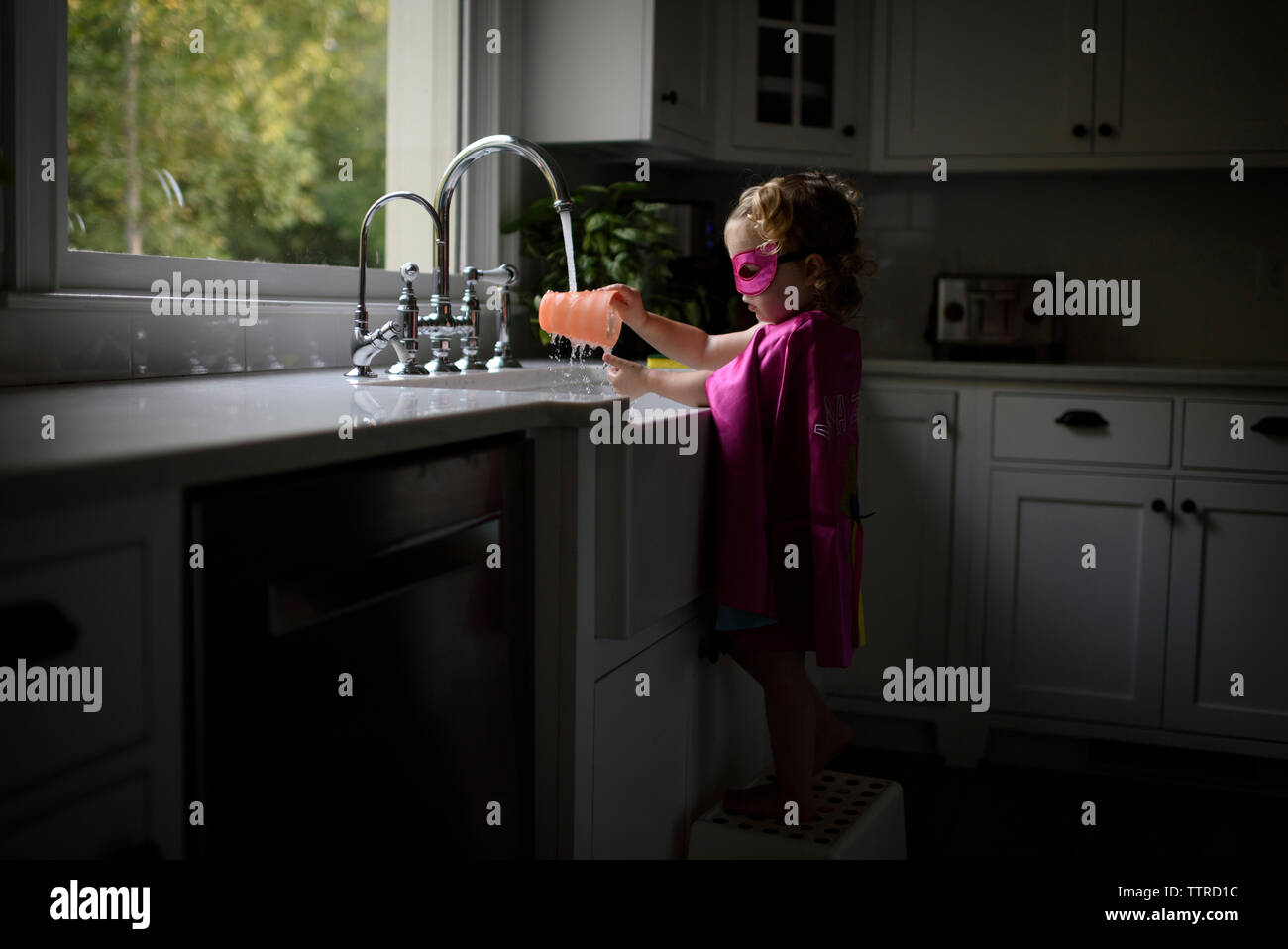 Side view of girl wearing superhero costume washing hands in kitchen sink while standing at home Stock Photo