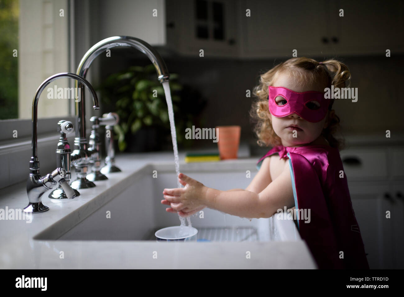 Portrait of girl wearing superhero costume washing hands in kitchen sink while standing at home Stock Photo