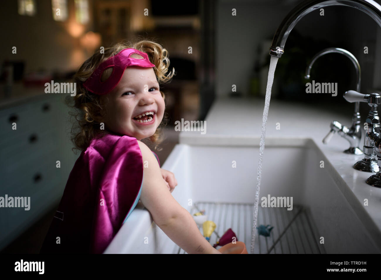 Portrait of smiling girl wearing superhero costume washing hands in kitchen sink at home Stock Photo