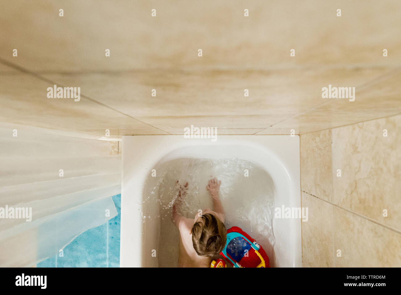 Overhead view of boy playing with toys in bath tub - Stock Image