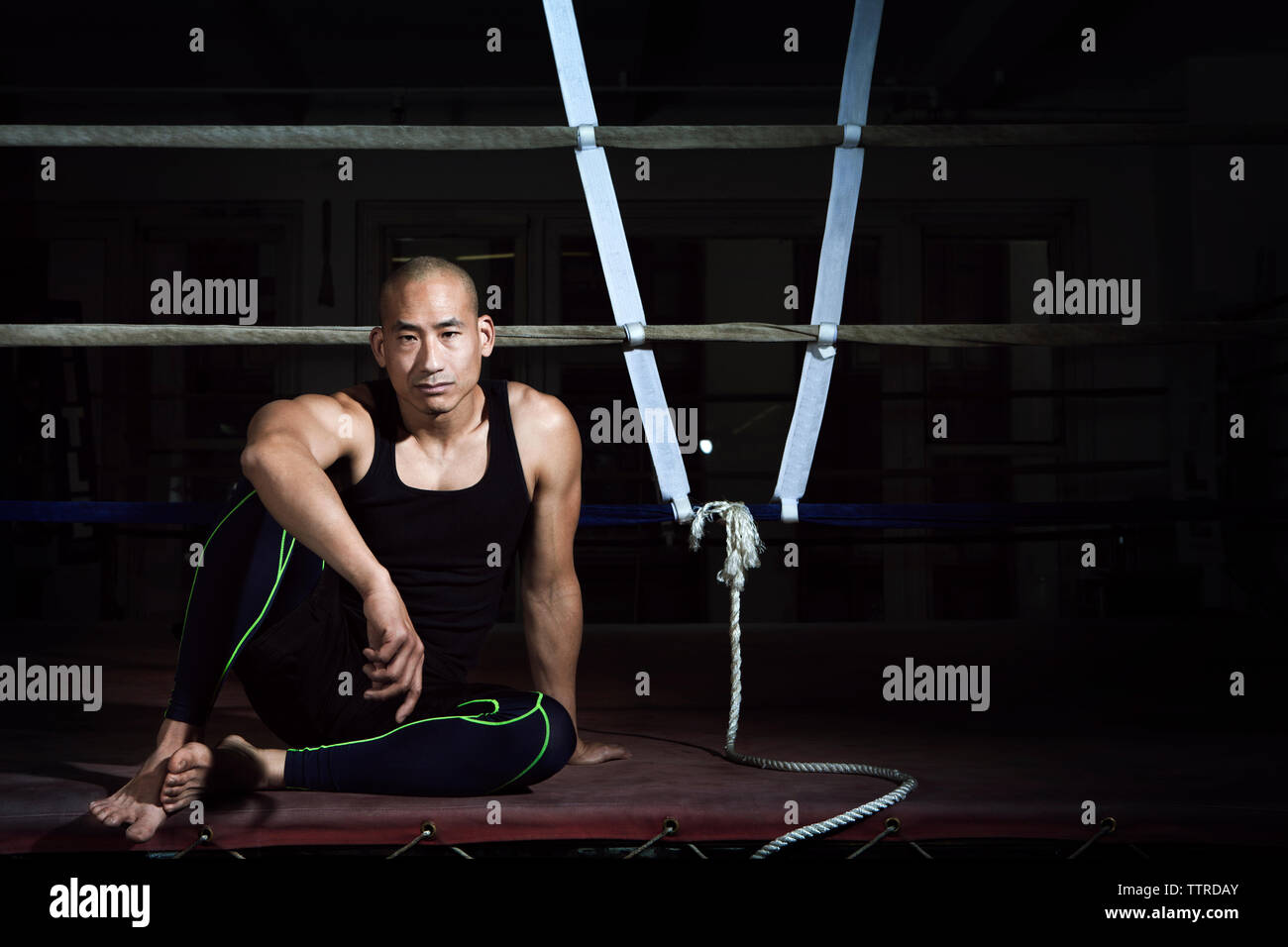 Confident athlete sitting on bench against boxing ring in gym - Stock Image