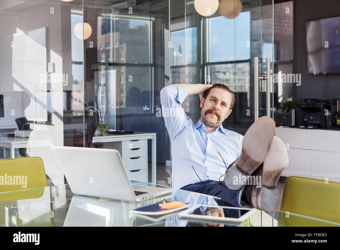 Relaxed businessman sitting with feet up on conference table in board room - Stock Image