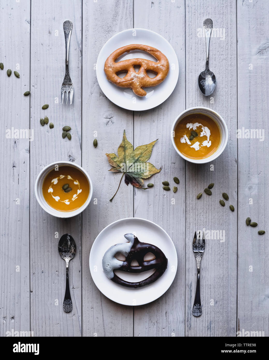 Overhead view of pretzels served with pumpkin soups on table - Stock Image