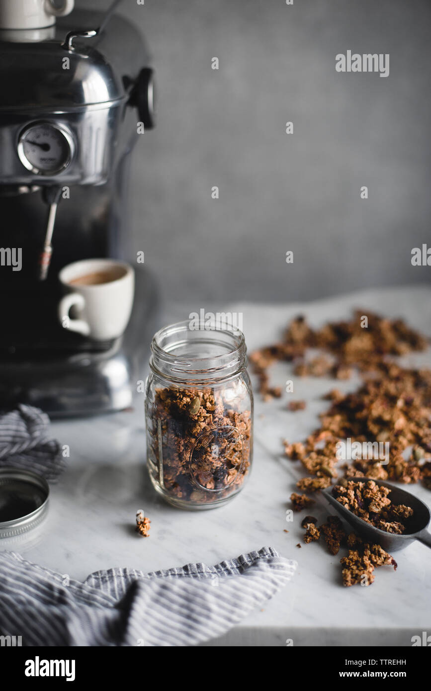 Granola by coffee maker on table - Stock Image