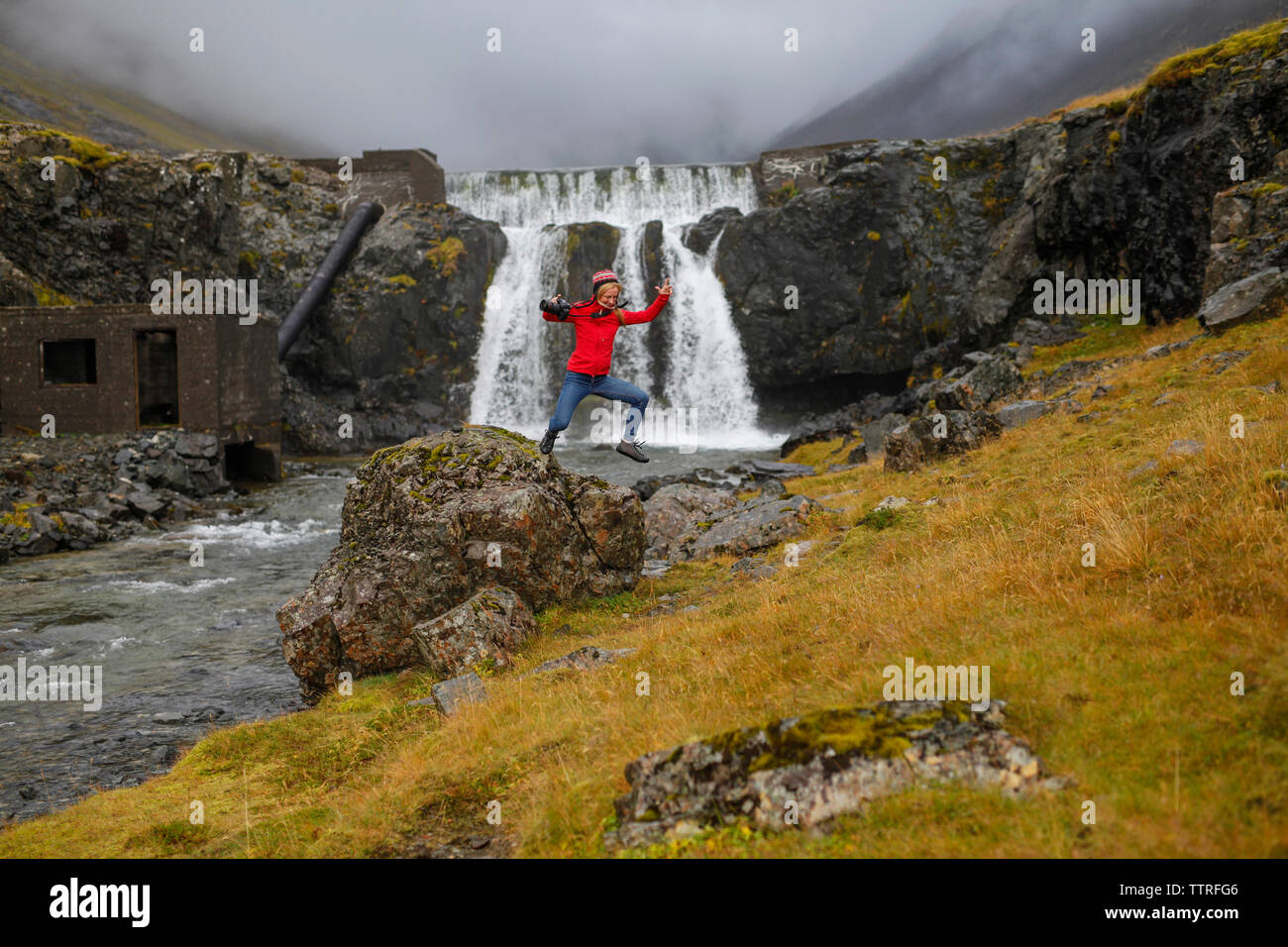 Excited female hiker jumping from rock against waterfall - Stock Image