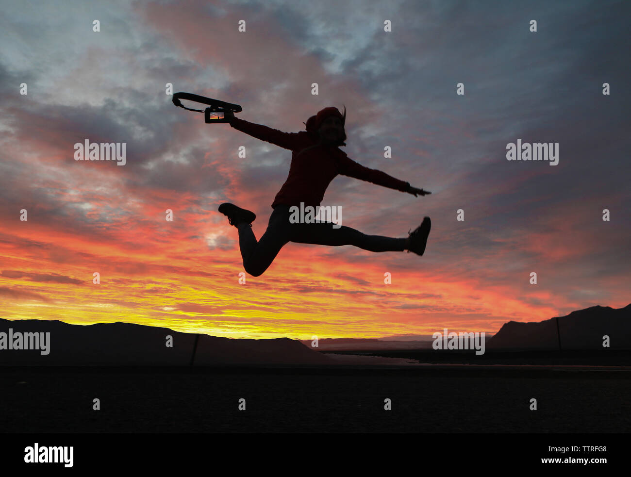 Excited hiker holding camera while jumping against dramatic sky - Stock Image