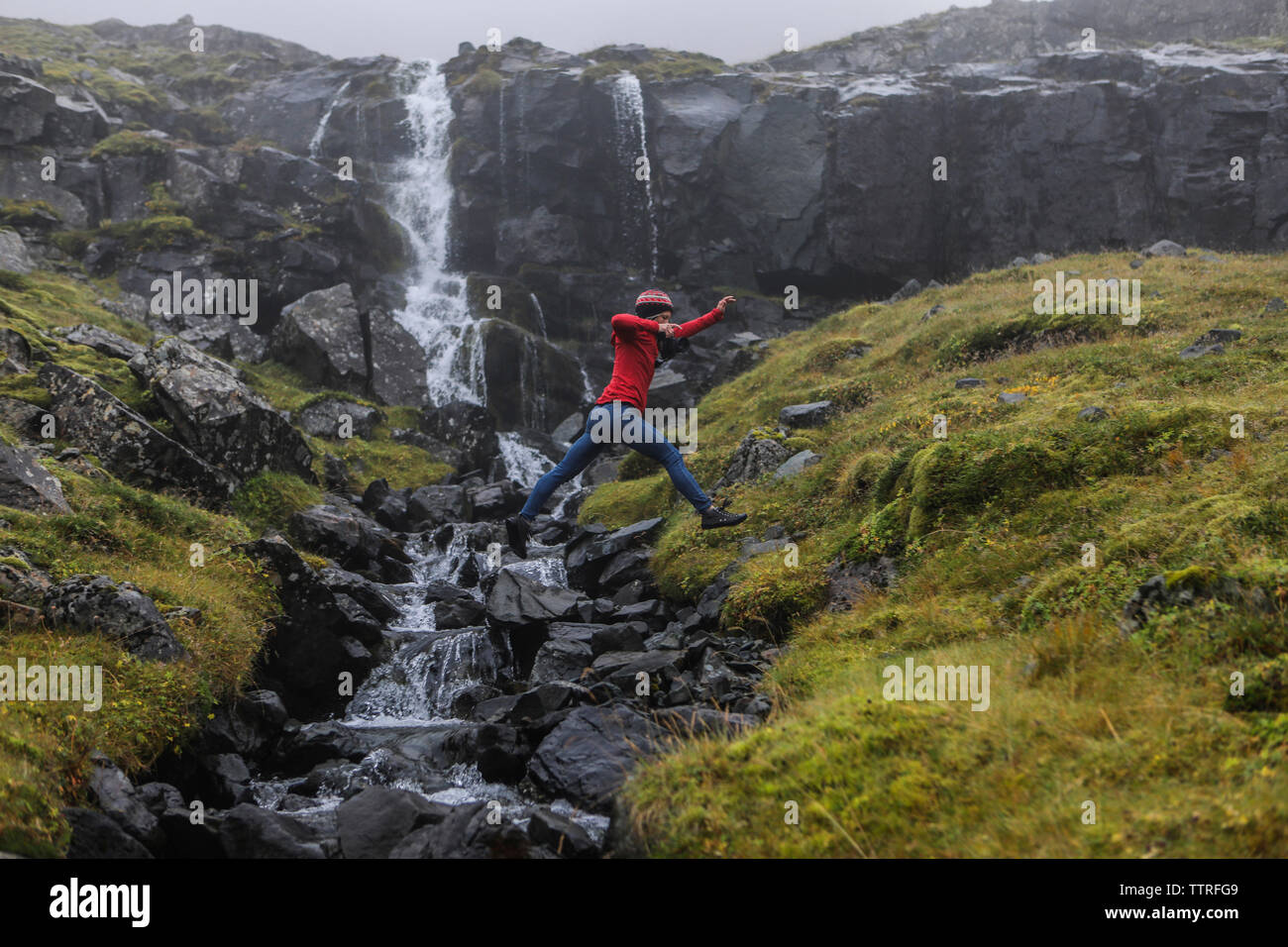 Side view of hiker jumping against waterfall - Stock Image