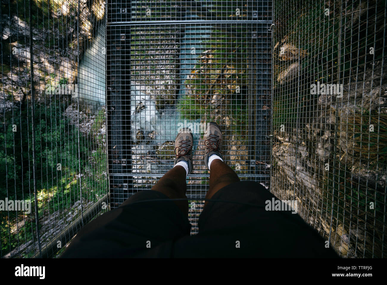 Low section of hiker on metallic footbridge over stream at forest - Stock Image