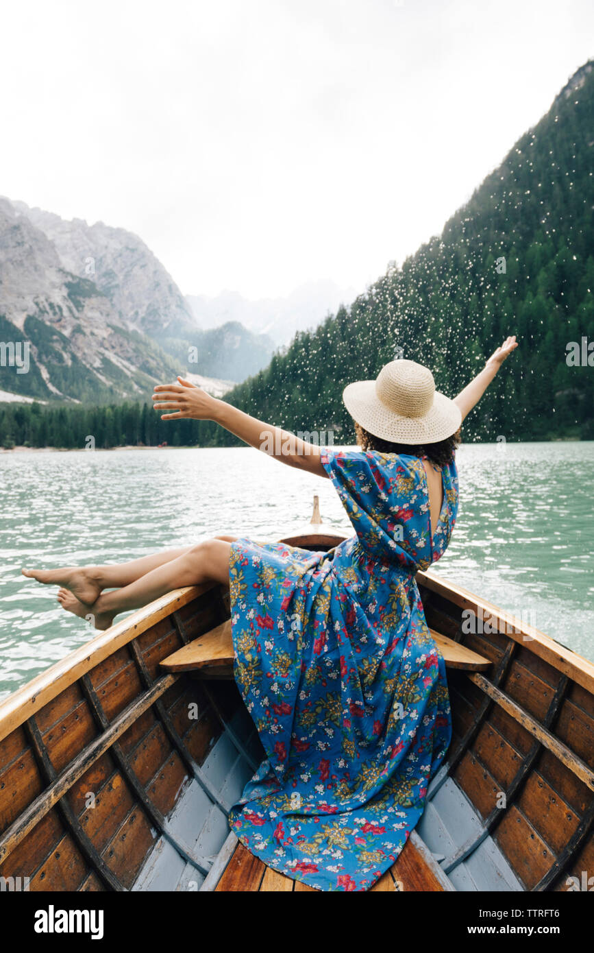 Happy woman enjoying rowboat riding over lake against mountains - Stock Image