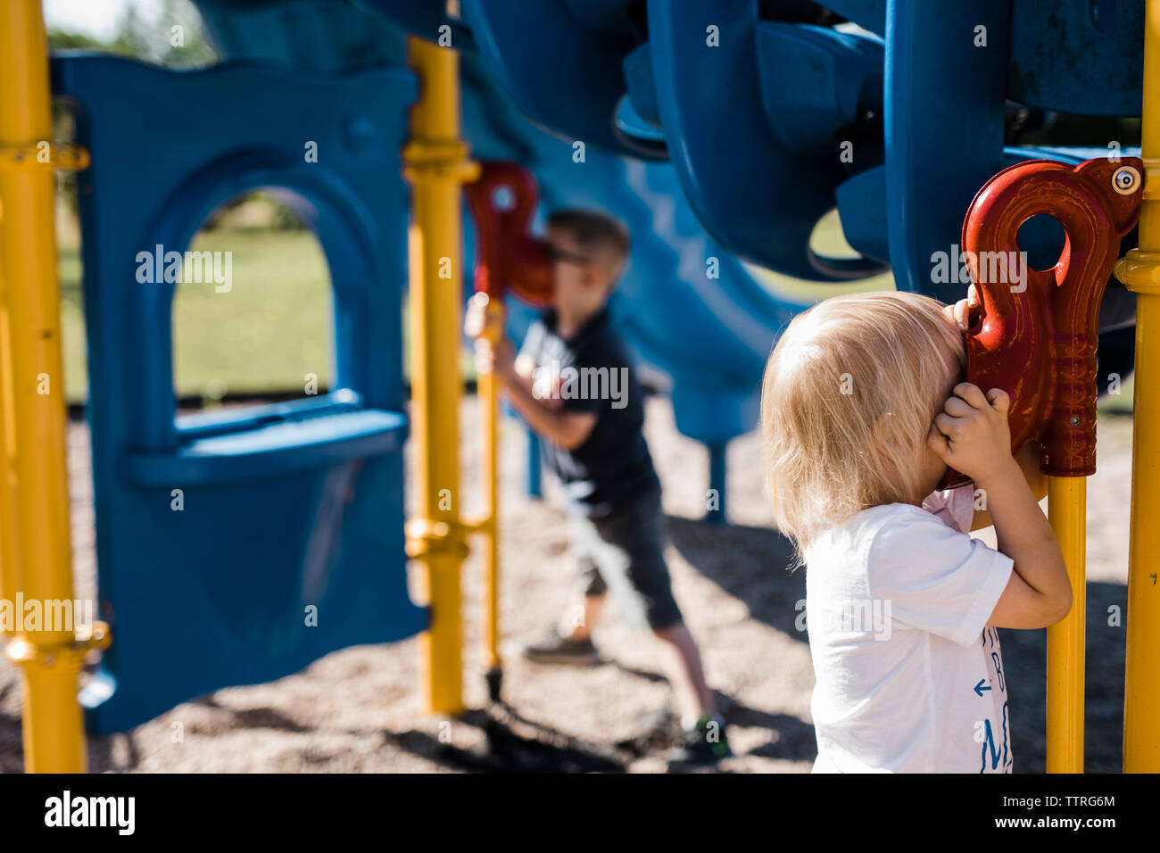 Brothers playing on outdoor play equipment at playground - Stock Image