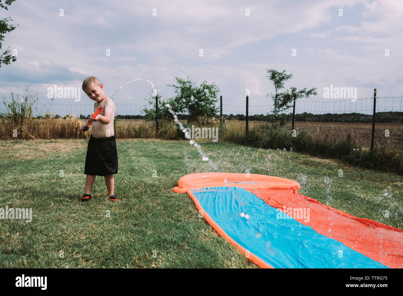 Boy playing with squirt gun by water slide at yard - Stock Image