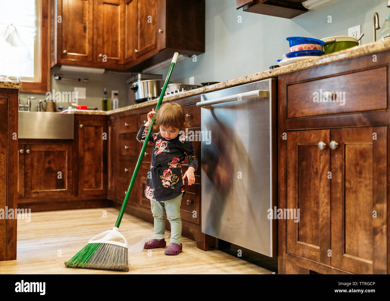 Girl cleaning kitchen with mop at home - Stock Image