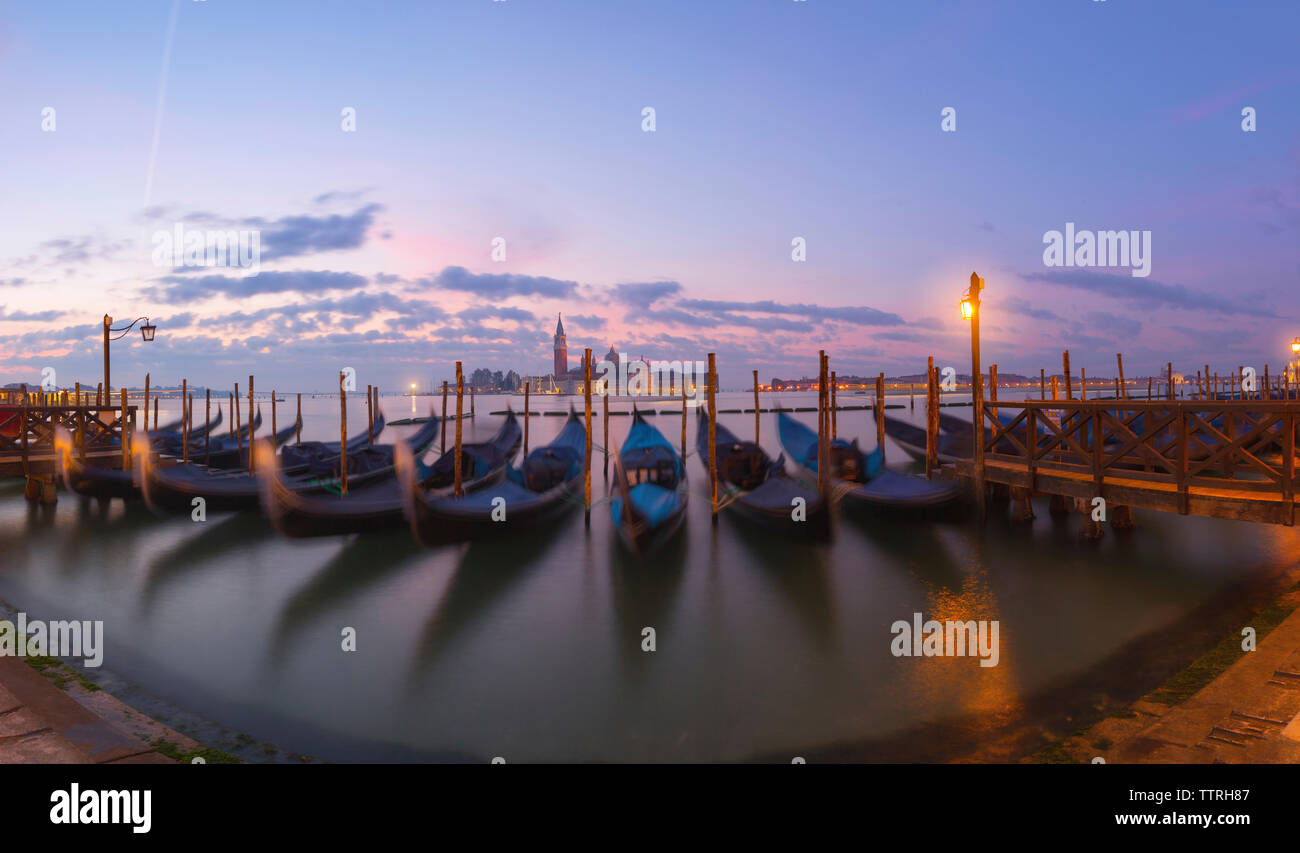 Gondolas moored on Grand Canal against sky during sunrise Stock Photo